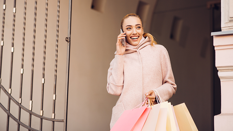 young-woman-talking-on-phone-after-shopping-in-N3F28SX