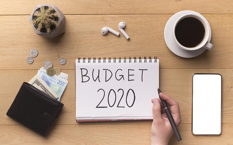 woman-hand-writing-new-year-budget-on-notepad-FRGJYXH