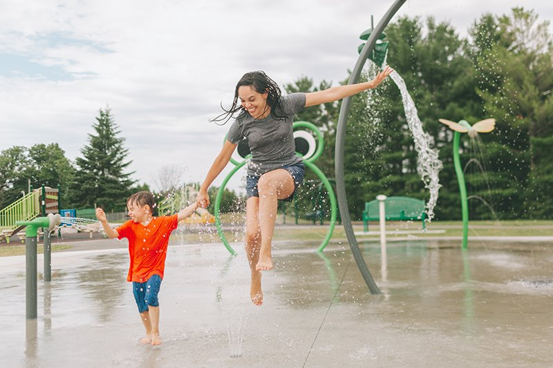 a-mother-and-son-running-through-a-water-park-GJYWLEW