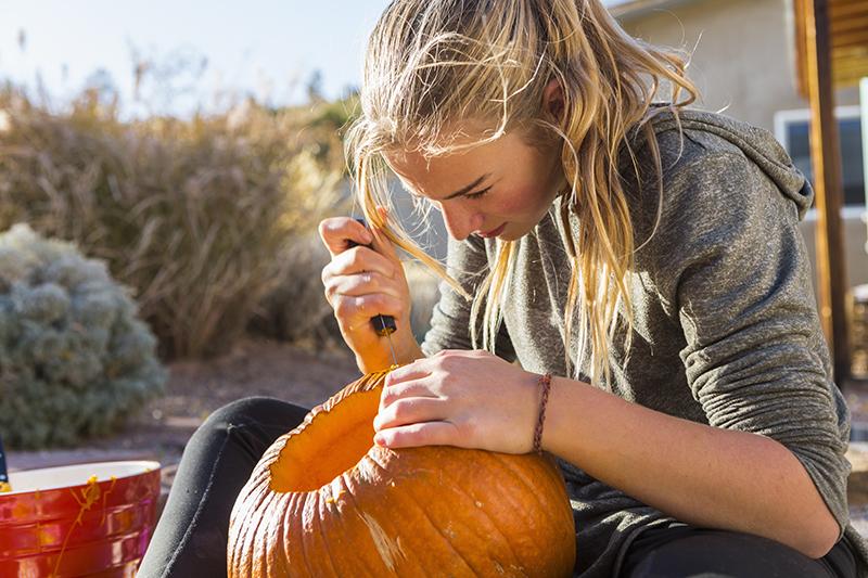 a-teenage-girl-carving-a-pumpkin-at-halloween-KCEEVUC
