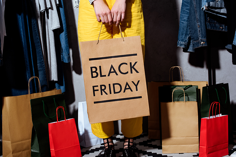 low-section-of-girl-with-shopping-bags-and-clothes